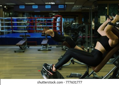 Woman in hack machine squatting and man doing extension