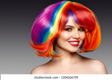 Woman hair as color splash. Rainbow up do short haircut. Beautiful young girl model with glowing  healthy skin.