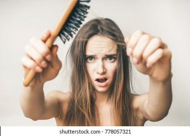 Woman with hair comb loss, upset on a white background