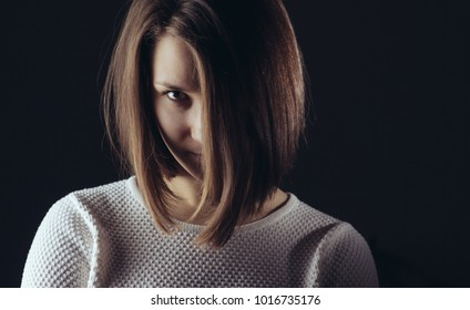 Woman hair covered face portrait in studio on dark background
