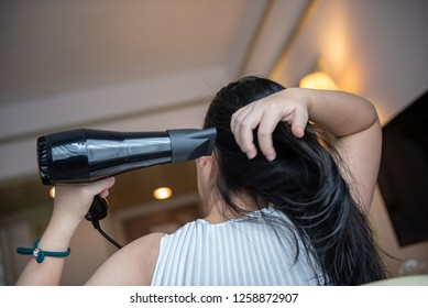 Woman with a hair dryer to heat the hair