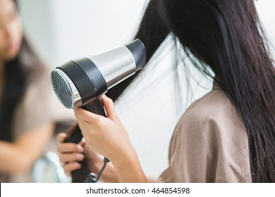 Woman with a hair dryer to heat the hair.