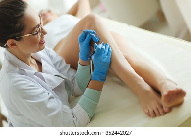 Woman with hair removal beauty clinic on foot