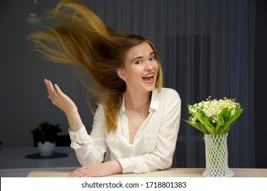 Woman with hair stand on end in white shirt near bouquet of flowers lilies of the valley
