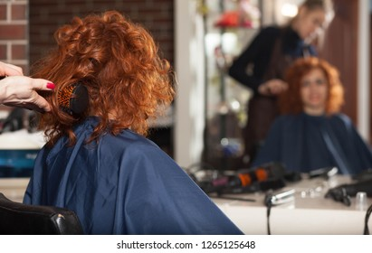 The woman in the hairdresser makes a new hairstyle. Reflection in the mirror blurred