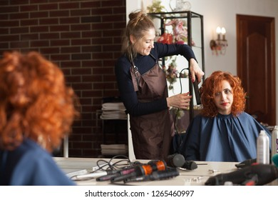 The woman in the hairdresser makes a new hairstyle. Reflection in the mirror, hairdresser master makes a new hairstyle