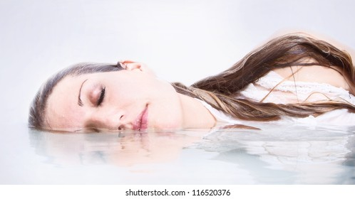 Woman half submerged in water with reflection