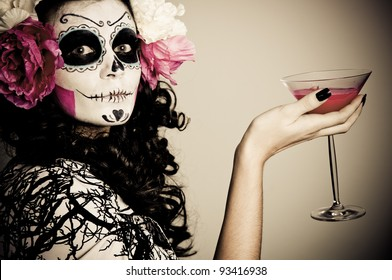 A woman in Halloween costume Holding a Glass With Red Liquid