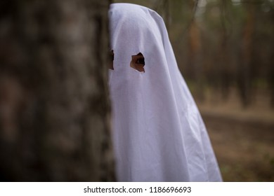 Woman in halloween ghost costume in the forest.