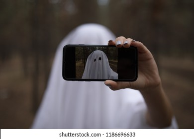 Woman in halloween ghost costume make selfie in the forest.