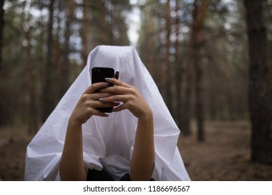 Woman in halloween ghost costume using smartphone in the forest.