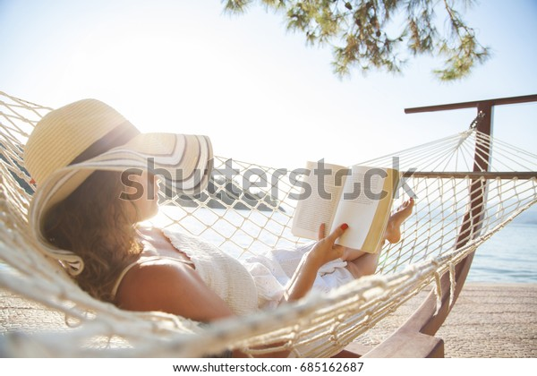 Woman in a hammock with book on summer day