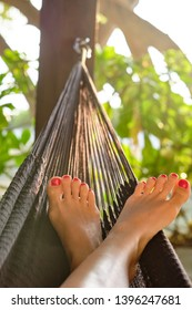 Woman in hammock on tropical beach. Legs close up. Summer vacation at Maldives.