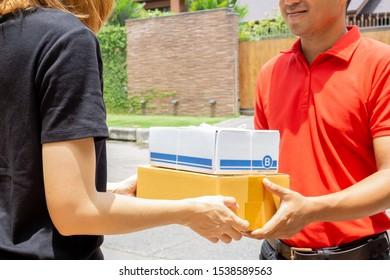 Woman hand accepting a delivery of boxes from deliveryman in red uniforms.