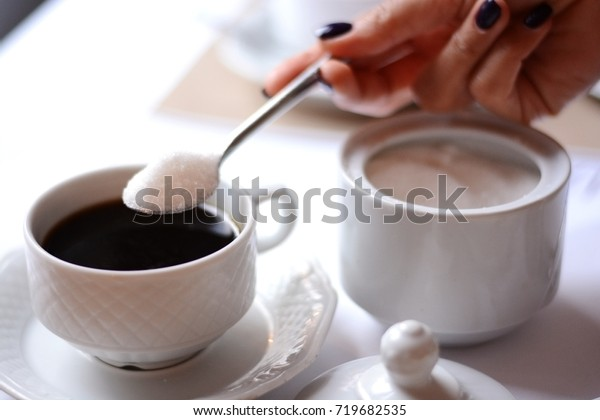 Woman hand adding a lot of sugar in a coffee from a sugar bowl, suggesting sugar overdose or unhealthy diet concept