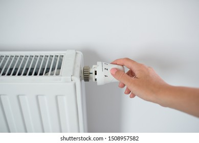 Woman Hand Adjusting The Knob Of Heating Radiator. The valve from the radiator - Heating. Hand adjusting thermostat valve of heating radiator in a room. Copy space.