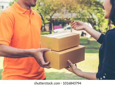 Woman hand appending receive sign signature after accepting a delivery of boxes from delivery man in uniform holding package, sign and receive delivery concept