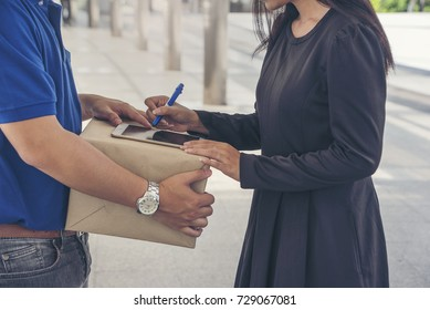 woman hand appending receive sign signature after accepting a delivery of boxes from delivery man in  blue uniform holding package, sign and receive delivery concept