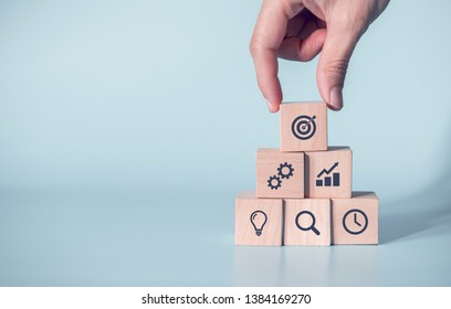 Woman hand arranging wood block with icon business strategy and Action plan, copy space.