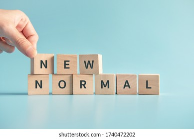 Woman hand arranging wooden cubes with NEW NORMAL word. Adapting to new life or business post-lockdown after coronavirus pandemic. Business with social distancing personal hygiene. - Shutterstock ID 1740472202