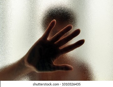 Woman hand behind the glass, concept stop abusing women, not home violence