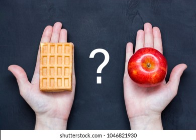 Woman hand with Belgian waffle and red apple fruit choosing, make right dietary choice. Weight loss diet dilemma gluttony concept. Diet. Healthy and Unhealthy Food. Weight Loss. Obesity.