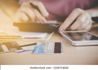 woman hand calculating  her expenses and debt from credit cards with smart phone on desk