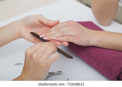 Woman Hand Care. Closeup Of Beautiful Female Hands Having Spa Manicure At Beauty Salon. Beautician Filing Clients Healthy Natural Nails With Nail File. Nail Treatment. High Resolution