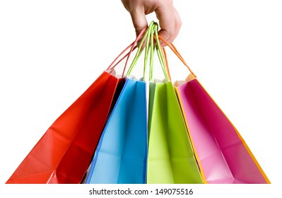 Woman hand carrying a bunch of shopping bags isolated on white