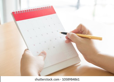 Woman hand carrying calendar and pointing on it by pen