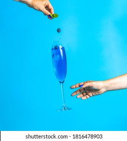 Woman hand catch fly wineglass of blue champagne  on a blue background with splash, juice blueberries falling in glass. Summer art food concept.