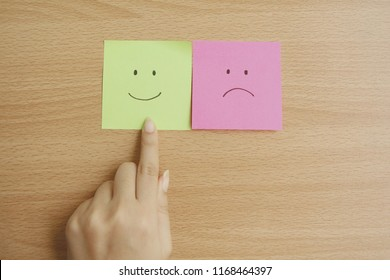 Woman hand choose happy feedback,Post-it paper note smile and sad face emotion.
