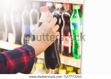 woman hand choosing cold soft drink or beverage on shelves in supermarket store.