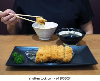 Woman hand with chopsticks picks piece of delicious fried pork, or tonkatsu ready to eat with hot streamed rice. . Japanese traditional food with selective focus.