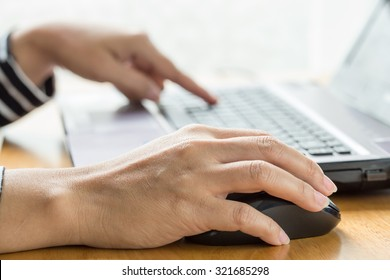 Woman hand click mouse and laptop