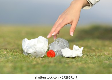 Woman hand collecting garbage of the grass in the mountain with copy space