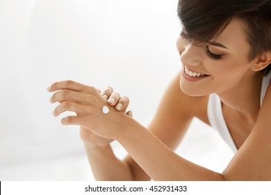 Woman Hand With Cream. Closeup Portrait Of Beautiful Happy Girl With Nude Makeup And Natural Manicure Nails Applying Cosmetic Moisturizing Hand Lotion On Soft Silky Skin. Beauty And Body Care Concept