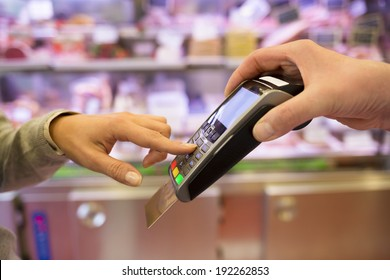 Woman hand with credit card swipe through terminal for sale, in market. code keyboard