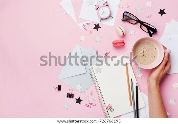 Woman hand with cup of coffee, macaron, office supply and empty notebook on pink pastel table top view. Flat lay style. Beautiful morning breakfast. Fashion female blogger working desk.