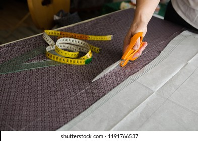Woman hand cuts a piece of fabric before sewing - scene with sewing tools: ruler, tailor inches, pattern and chalk