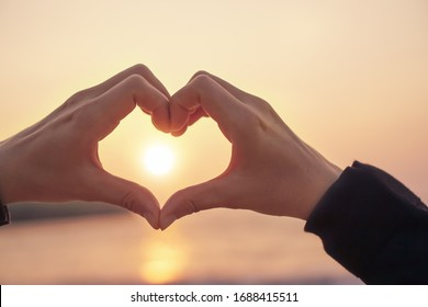 Woman hand do heart shape on sunset sky and bokeh background.