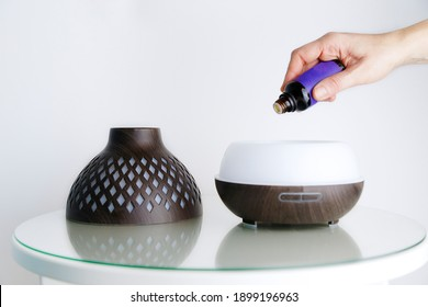 Woman hand dripping lavender essential oils into a diffuser