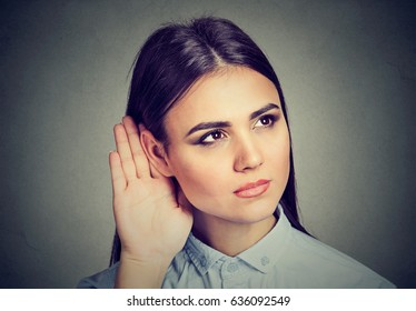 Woman with hand to ear gesture listening carefully