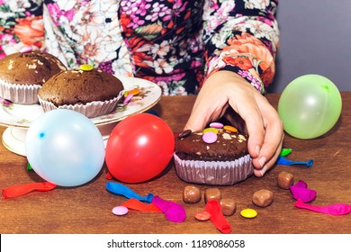 woman hand eating  chocolate arabic homemade cupcake, madeleine with colorful ballons and smarties. birthday party
