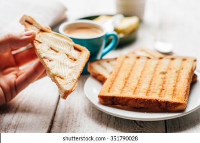 Woman hand eating coffee and toast with butter and jam for breakfast