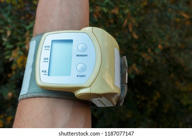 woman hand with electric tonometer measuring blood pressure. Medicine, age, healthcare and people concept with tonometer on the green background. The tonometer is on hand. Arterial pressure and proble