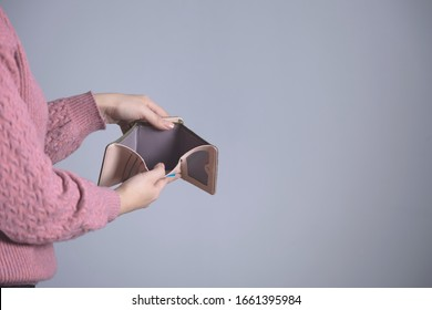 woman hand empty wallet on grey background