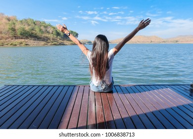 Woman hand up enjoyment beautiful view  in holiday by sit on the floor wood in the lake