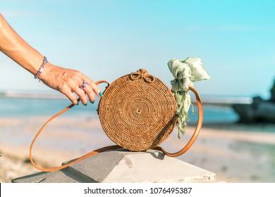 Woman hand with fashionable stylish rattan bag and silk scarf on the ocean background. Tropical island of Bali, Indonesia. Rattan handbag and silk scarf.