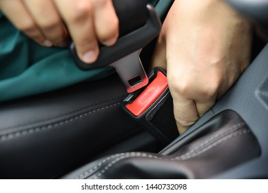 Woman hand fastening a seat belt in the car. Car safety concept.